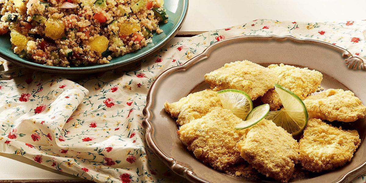 Fotografia em tons de dourado e branco de uma bancada branca com um prato dourado, sobre ele pedaços de peixe empanado com fatias de limão. Ao Lado um paninho branco florido.