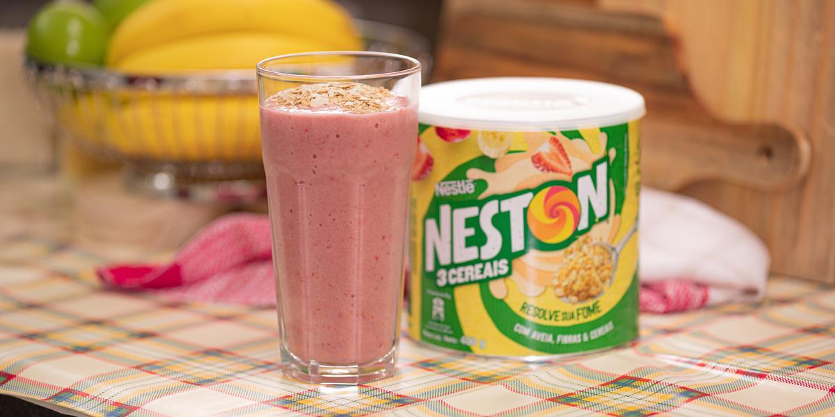 Foto de uma bancada, sobre ela há uma toalha xadrez de tonalidade rosa. No centro há um copo com uma bebida cremosa cor-de-rosa e, ao lado direito dela, uma lata de Neston 3 Cereais. Ao fundo vê-se algumas tábuas, bananas e limões.