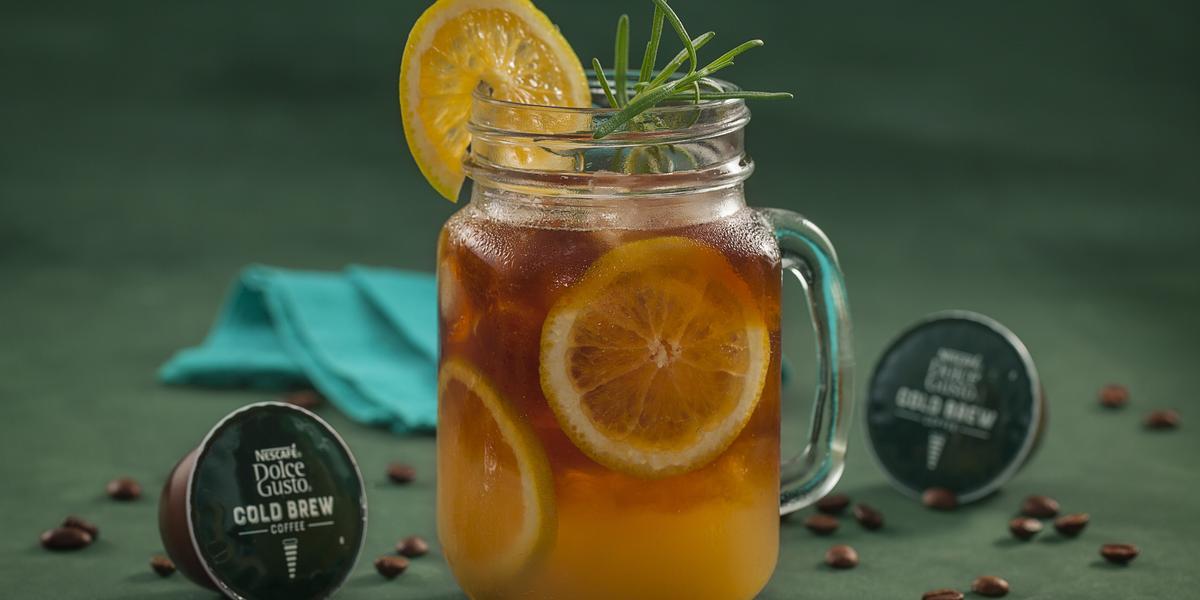 Fotografia em tons de verde de uma bancada verde, sobre ela um copo de vidro com cold brew com laranjas. Ao lado capsulas de Dolce Gusto Cold Brew e um paninho azul.