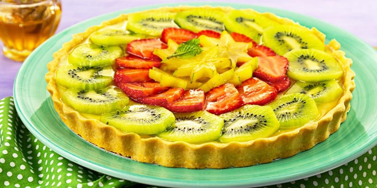 Fotografia em tons de verde e vermelho, com torta de frutas frescas fatiadas em prato verde sobre guardanapo verde com bolinhas brancas, potinho com mel ao fundo, tudo sobre bancada na cor cinza.