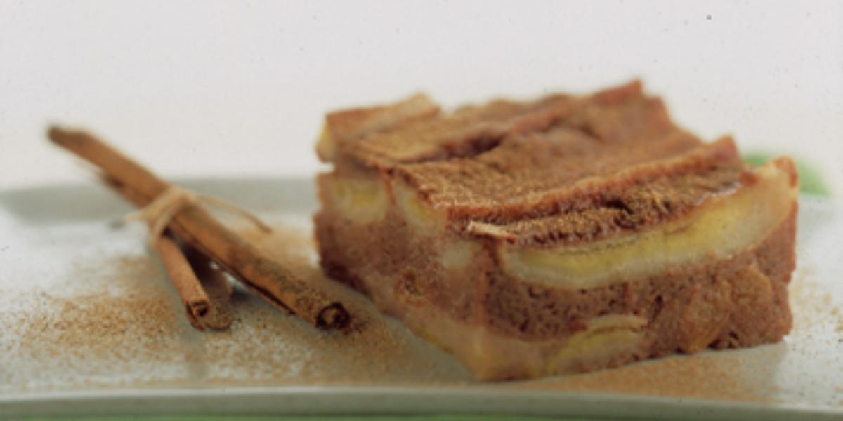 Fotografia em tons de canela e cinza, com pedaço de torta de banana com canela sobre travessa verde com ramos de canela ao lado, tudo polvilhado com canela, em fundo cinza.