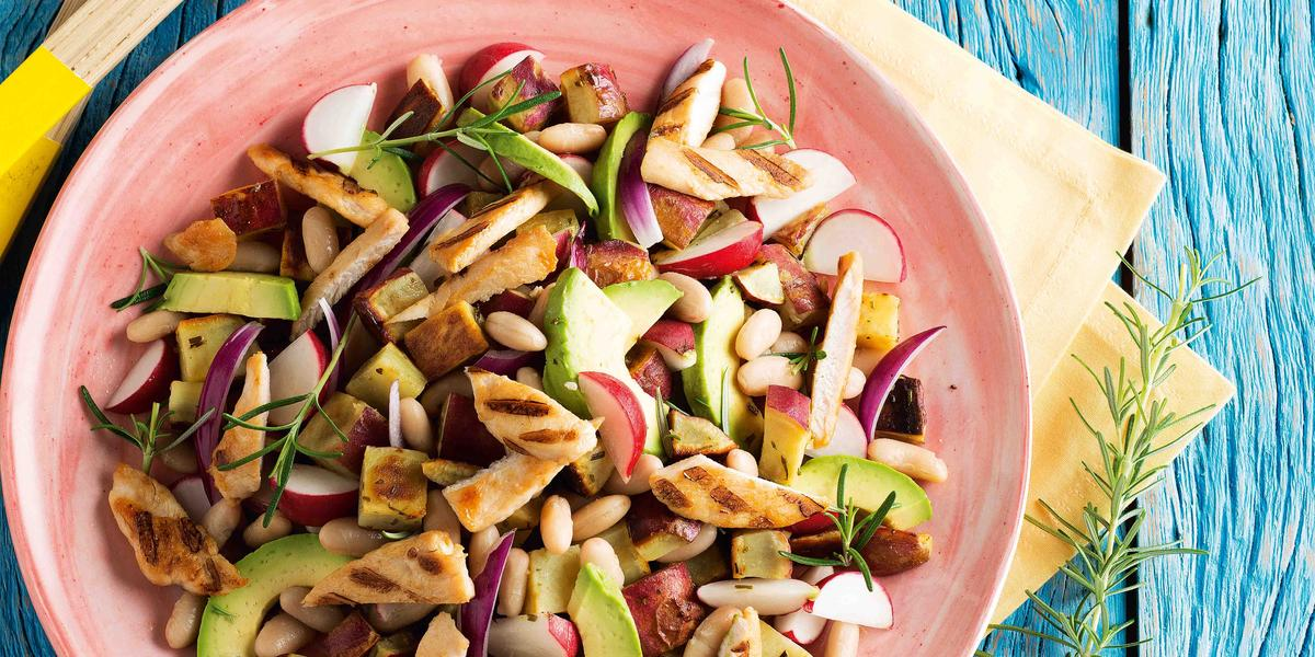 Fotografia em tons de azul e rosa em uma bancada de madeira azul com um prato rosa com salada de batata-doce, frango, feijão branco e abacate dentro dele.