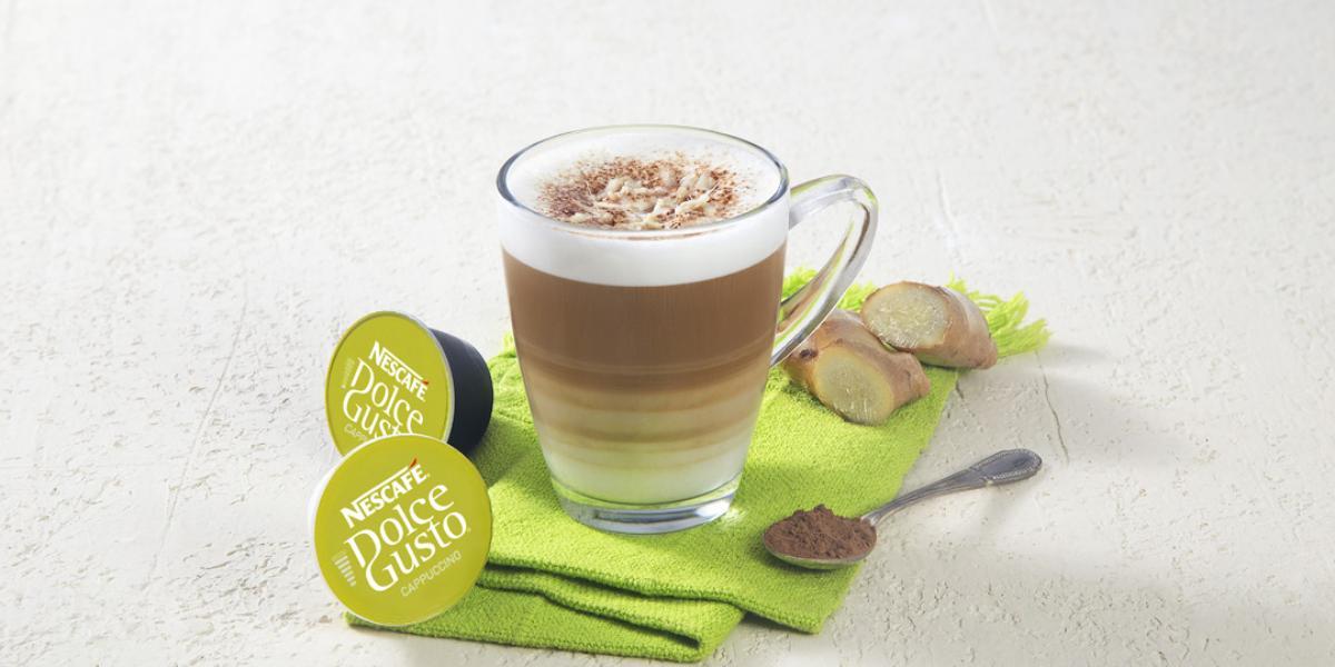 Fotografia em tons de verde em uma bancada de madeira clara com um pano verde e uma xícara de vidro com o cappuccino dentro dele. Ao lado, cápsulas de Dolce Gusto Cappuccino.