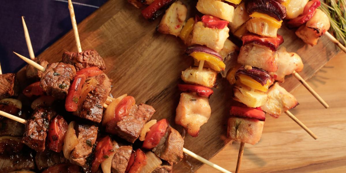 Foto de vários espetinhos de carne e de frango, um em cima do outro