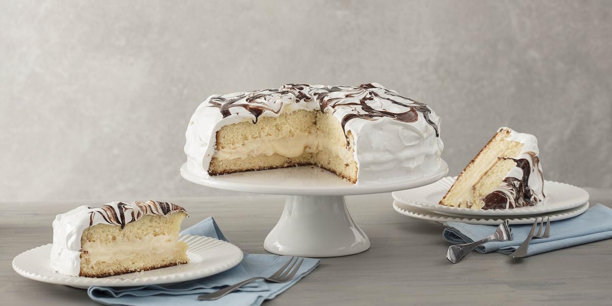 Fotografia em tons de branco, azul e cinza, ao centro boleira com torta fatiada, em ambos os lados pratos com pedaços da torta sobre guardanapos azuis e garfos, tudo sobre bancada e fundo em tons de cinza.