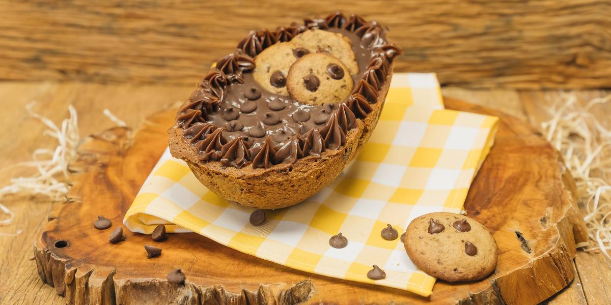 Fotografia em tons de marrom de uma bancada marrom com uma tábua de madeira com um paninho amarelo e branco, sobre ele um ovo recheado de cookie. Ao lado um cookie.