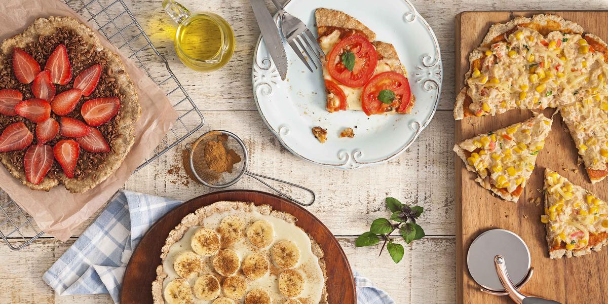 fotografia em tons de bege de uma bancada vista de cima, contém uma tábua redondo e marrom com uma pizza com fatias de banana, uma grade com uma pizza de chocolate e fatias de morango e um prato redondo e branco com uma fatia de pizza