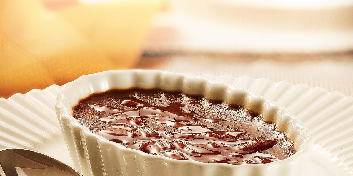fotografia em tons de branco e marrom de uma bancada vista de frente, contém um prato redondo e branco com um potinho oval branco com um creme de chocolate dentro e uma colher ao lado para servir.