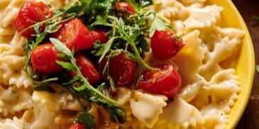 Farfalle z pomidorkami, rucolą i sosem serowym