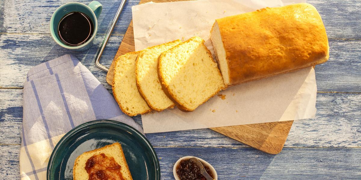 Fotografia em tons de azul e branco de uma bancada azul com uma tábua, sobre ela um paninho branco com o pão. Ao lado um paninho branco e azul, sobre ele um prato redondo azul com uma fatia de pão e geleia e uma xícara de café.