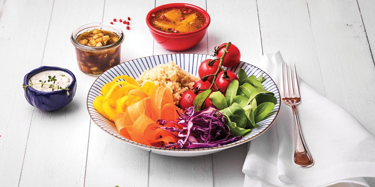 Fotografia em tons coloridos em uma bancada de madeira branca com um prato fundo com listras azuis e salada de rúcula, cenoura, cebola roxa e tomate dentro dele. Ao lado, potinhos com opções de molhos.