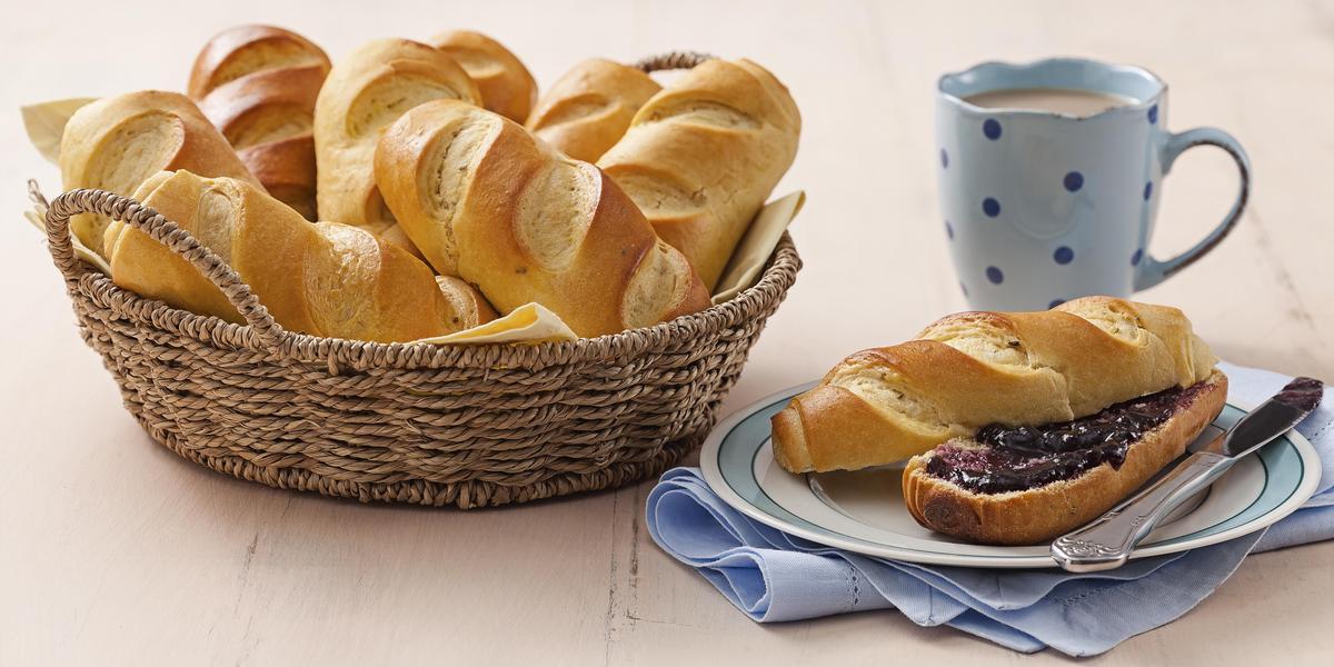 Fotografia em tons de azul em uma bancada de madeira clara, um pano azul, um prato branco redondo com detalhes em azul e um pão doce aberto com geleia no meio em cima dele. Ao lado, uma cesta de vime com vários pães e uma xícara azul com café.