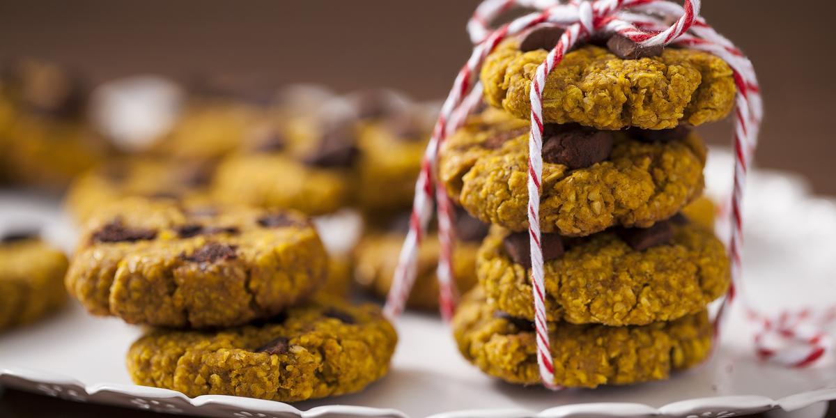 Fotografia em tons de amarelo em uma bancada de madeira com um recipiente branco raso e vários cookies integrais de aveia e abóbora em cima dele.