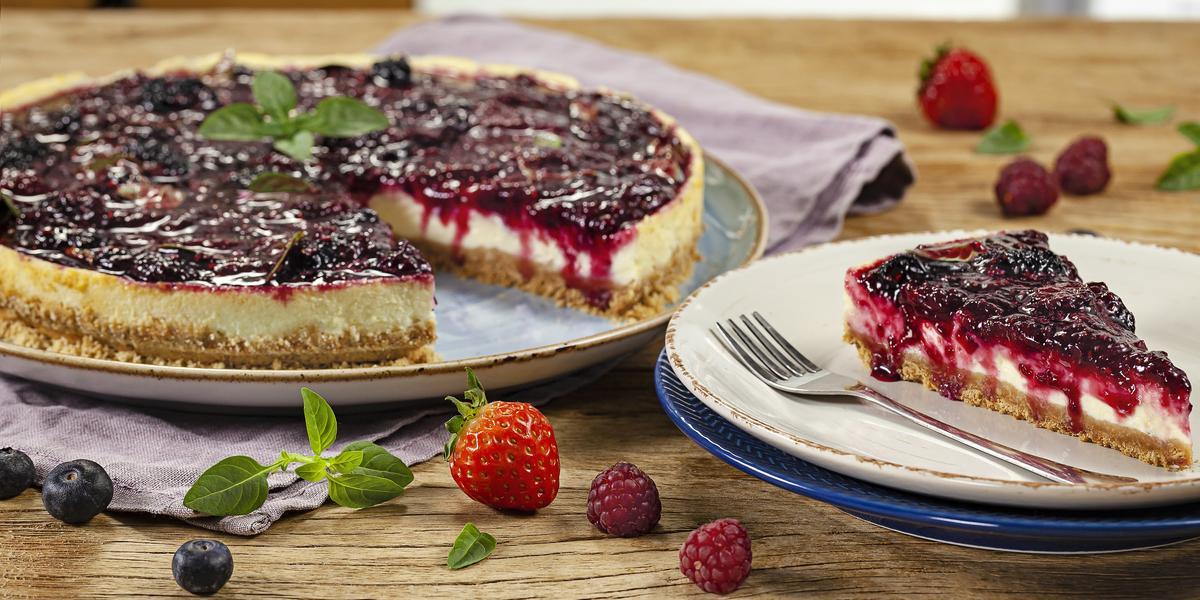 Fotografia em tons de vermelho em uma bancada de madeira com um prato raso grande com a cheesecake de iogurte com frutas vermelhas e um prato raso pequeno com uma fatia da cheesecake. Morangos e uvas espalhadas pela bancada.