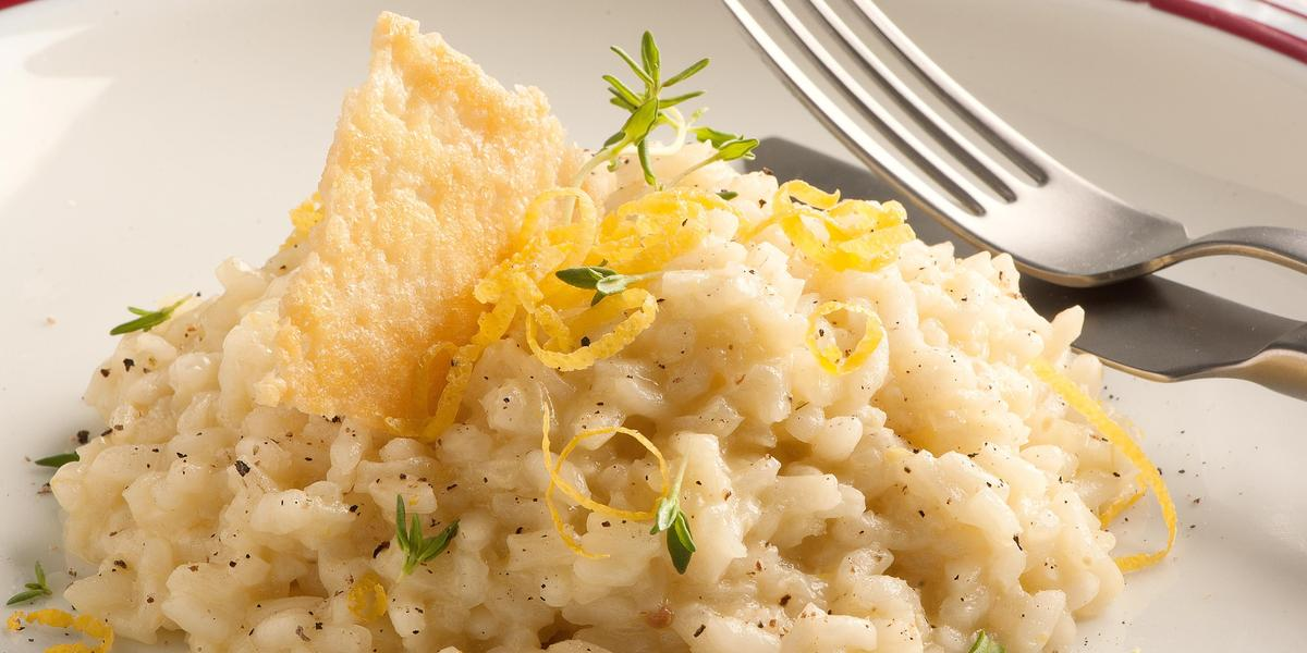 Fotografia de um prato branco com uma listra vermelha na borda, onde está servido o risoto decorando com raspas de limão siciliano e uma crosta crocante de queijo parmesão. Ao fundo uma taça de vidro transparente e um guardanapo de tecido branco.