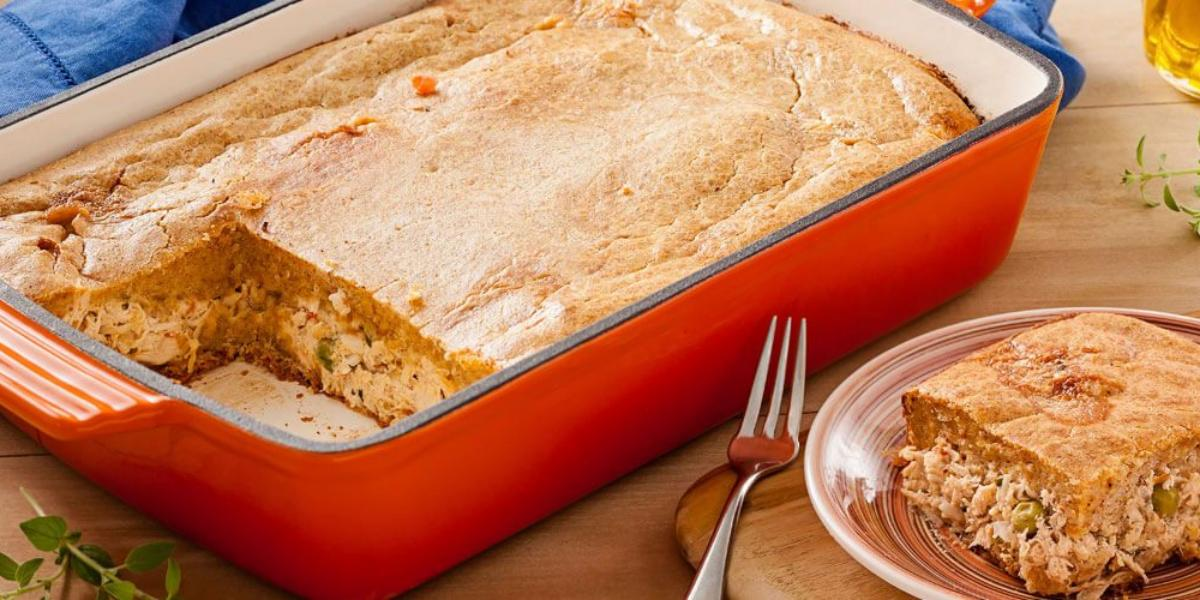Fotografia em tons de creme, vermelho e azul, ao centro uma travessa vermelha onde a torta foi preparada e servida. Ao lado está uma fatia da torta em uma prato de sobremesa e um garfo.