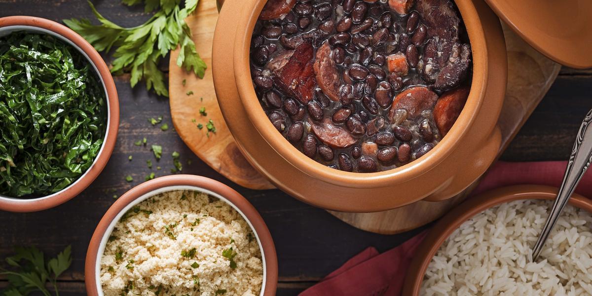 Fotografia em tons de preto e marrom de uma bancada de madeira escura, um pote com couve refogada, um pote com farofa, um pote com arroz branco e um pote com uma feijoada com feijão preto e várias carnes.