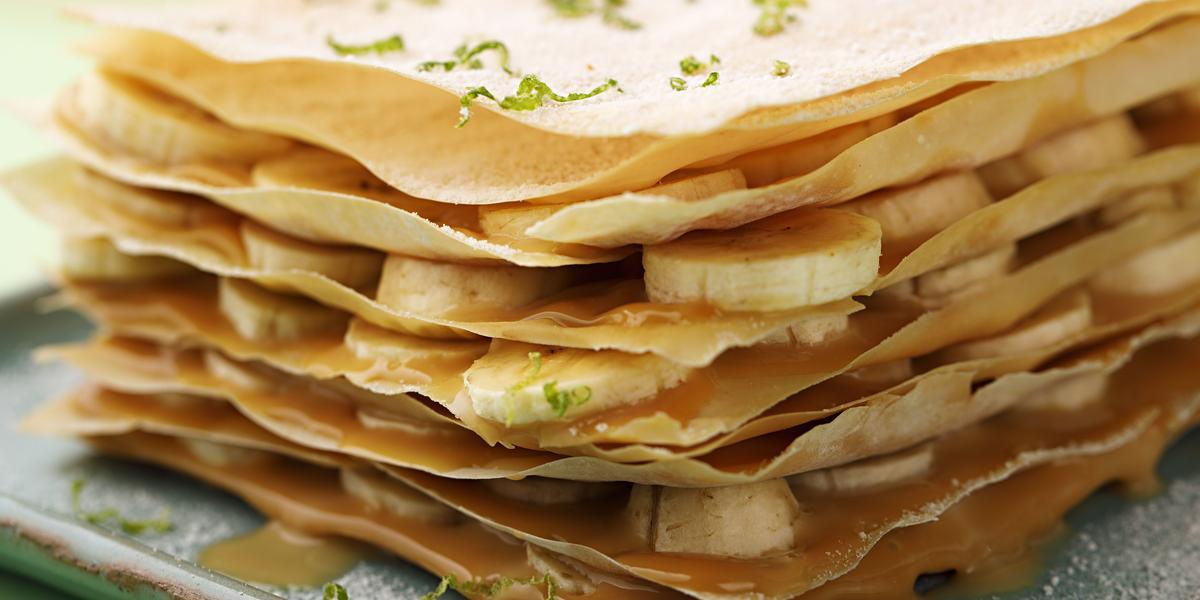 Fotografia em tons de verde em uma bancada de madeira com uma toalha verde, um prato quadrado com a torta crocante com recheio de doce de leite e bananas em rodelas.