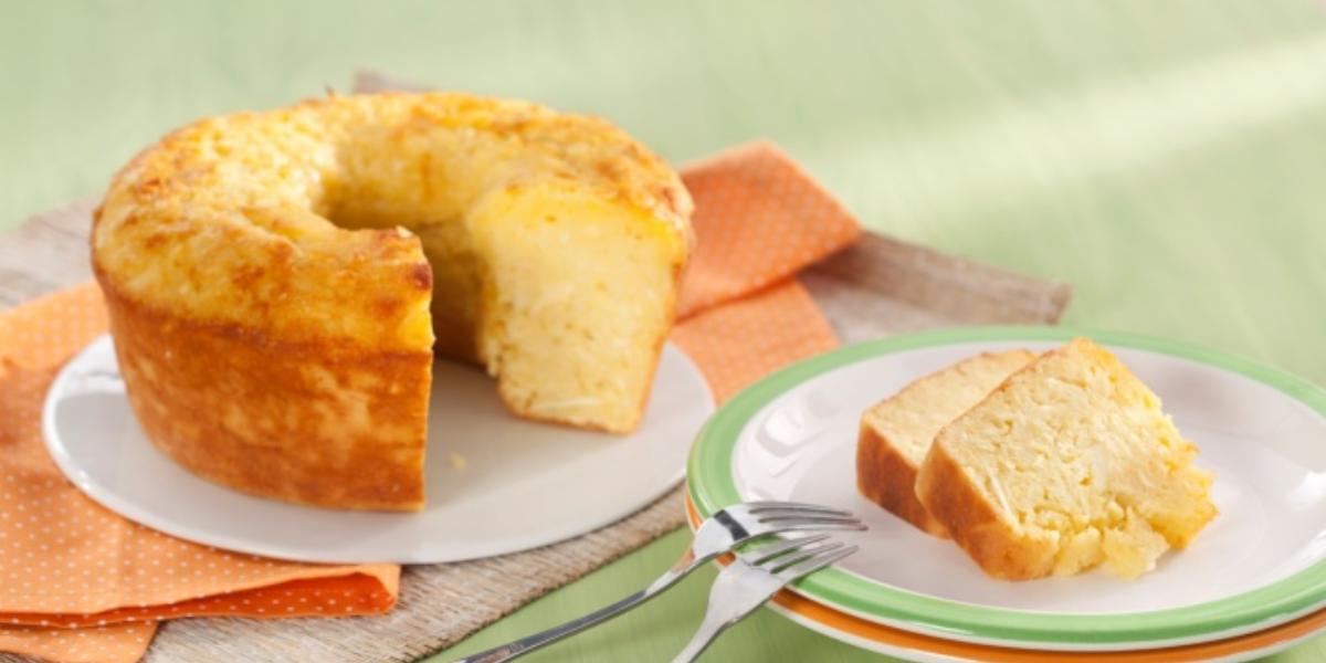 Fotografia em tons de laranja e verde em uma mesa de madeira verde com um pano laranja de bolinhas branca. Ao centro, um prato raso branco com o bolo de macaxeira cortado. Ao lado, um prato branco com borda verde e duas fatias do bolo.