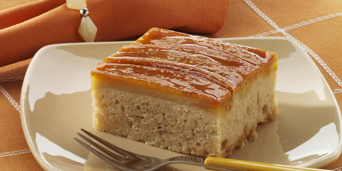 Foto de um prato branco em cima de uma toalha laranja com branco e com um pedaço de bolo de banana dentro com um garfo do lado