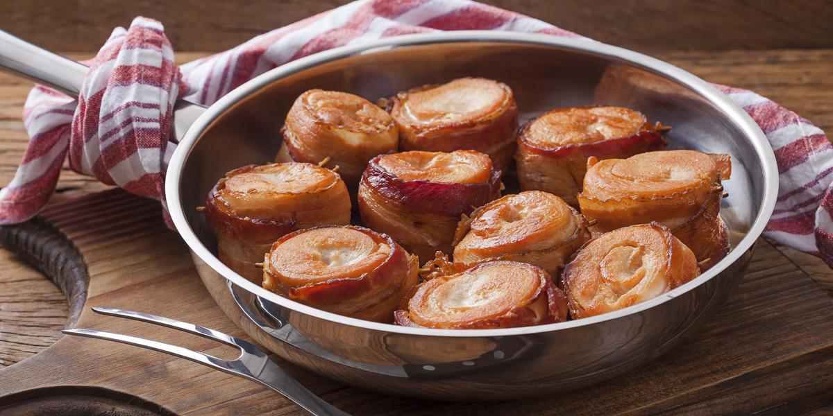 Fotografia em tons de marrom, prata e vermelho de uma bancada de madeira e uma tábua de madeira, sobre ela um panela de inox com medalhões de frango com bacon. Ao lado um garfo de servir, ao fundo um paninho branco e vermelho.
