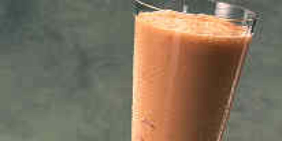 Fotografia em tons de vermelho em uma bancada de madeira, várias frutas vermelhas espalhadas e um copo de vidro super grande com a bebida feita com pitanga e Leite Moça dentro dele.