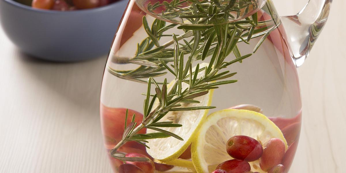 Fotografia em tons de branco, verde e roxo de uma bancada de madeira clara, ao centro uma jarra de vidro transparente com a água, limão, uva e o alecrim. Ao fundo em um recipiente azul as mesmas frutas estão dentro para decoração.
