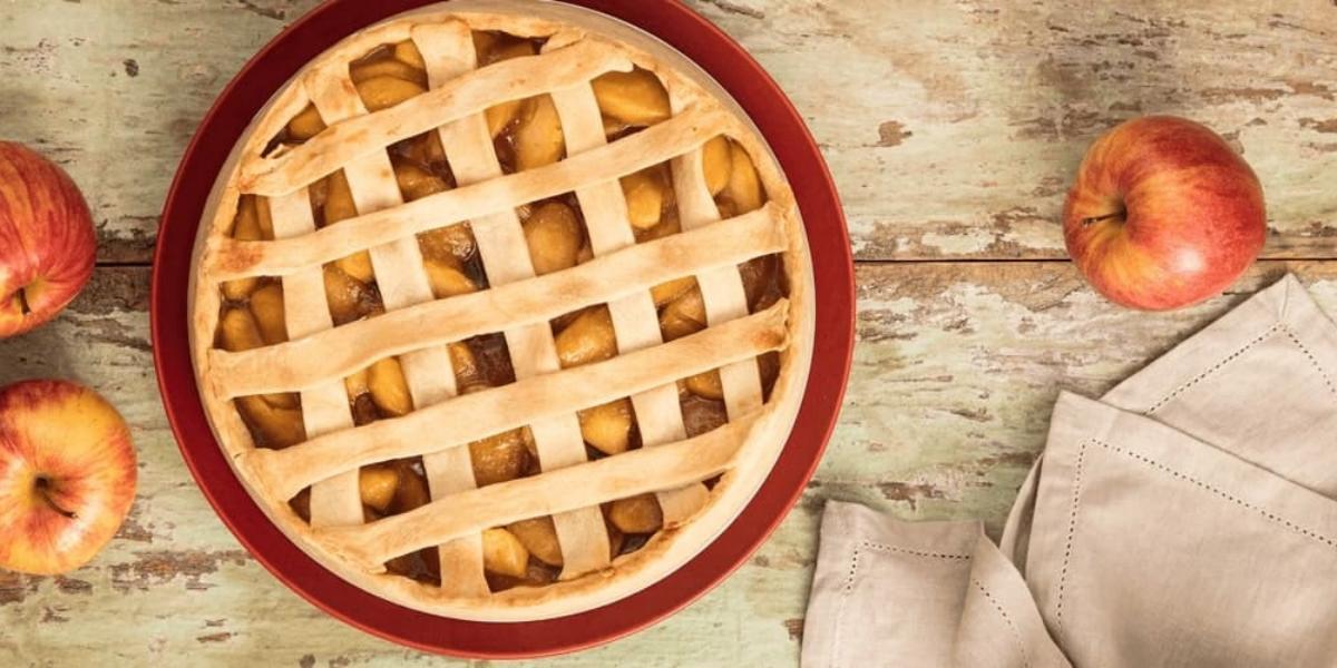 fotografia em tons de vermelho e bege de uma bancada bege vista de cima, contém um prato redondo vermelho com a torta recheada com pedaços de maça e 3 maças em volta e um pano bege.