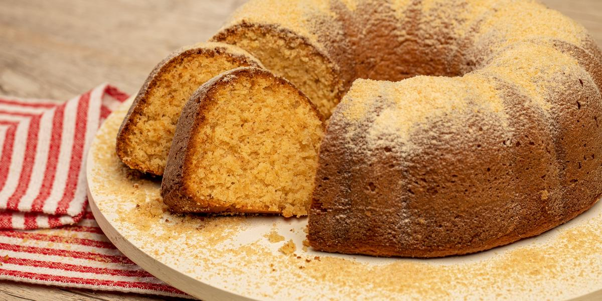 Foto de uma bancada de madeira. Sobre ela há um tabuleiro branco com um bolo polvilhado de Farina Láctea Nestlé e com duas fatias cortadas. Ao lado do tabuleiro há um tecido listrado vermelho e branco
