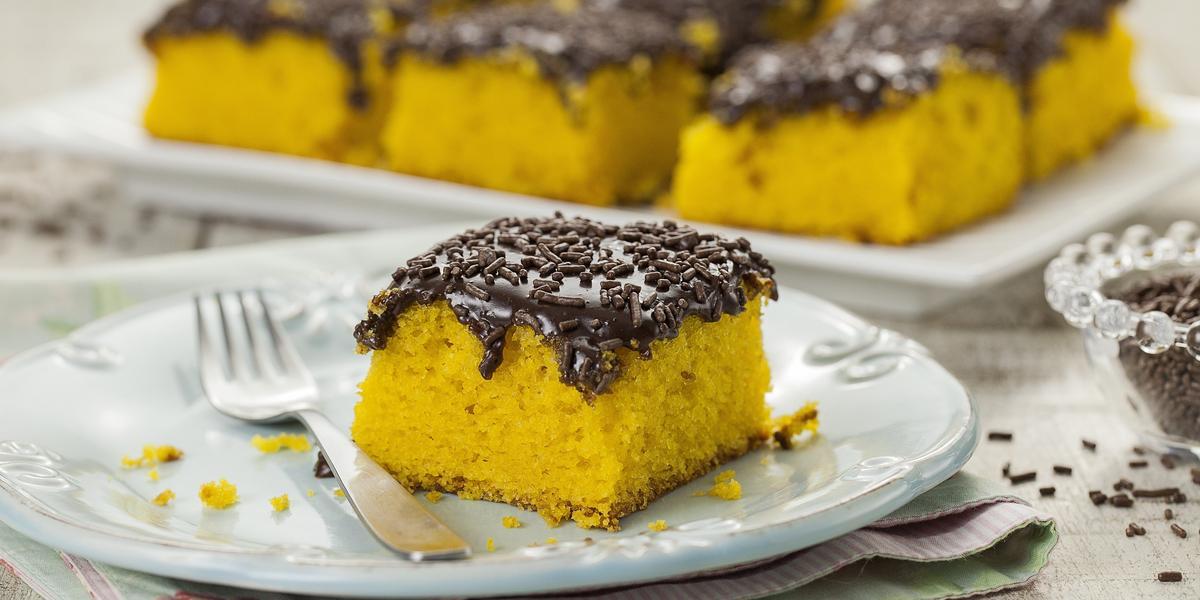 Foto de um pedaço de bolo de cenoura com cobertura de brigadeiro em um prato branco com um garfo do lado
