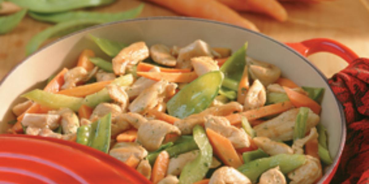 Fotografia em tons de vermelho e verde de uma mesa vista de cima, uma panela na cor vermelha ao lado uma tampa e pano da mesma cor. Dentro da panela contém pedaços de frango, cenoura e salsão. Ao fundo varias cenouras.