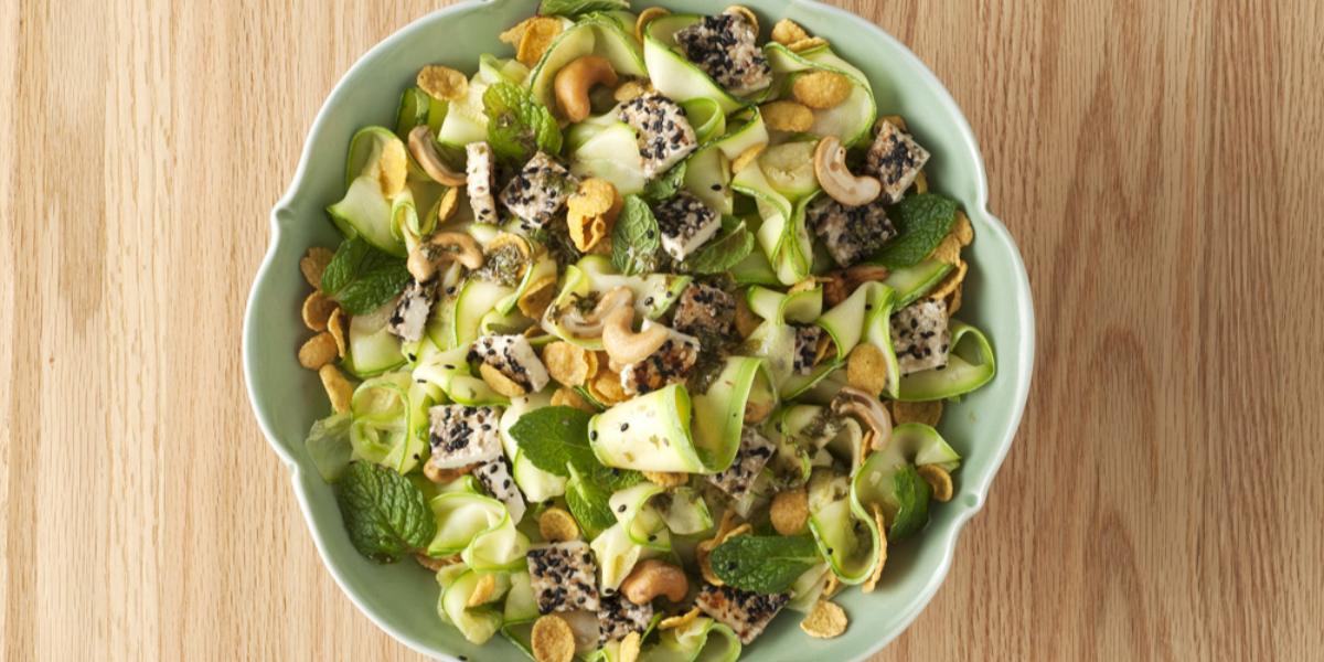 fotografia em tons de bege e verde de uma bancada vista de cima. Ao centro contém um recipiente redondo com salada de abobrinha.