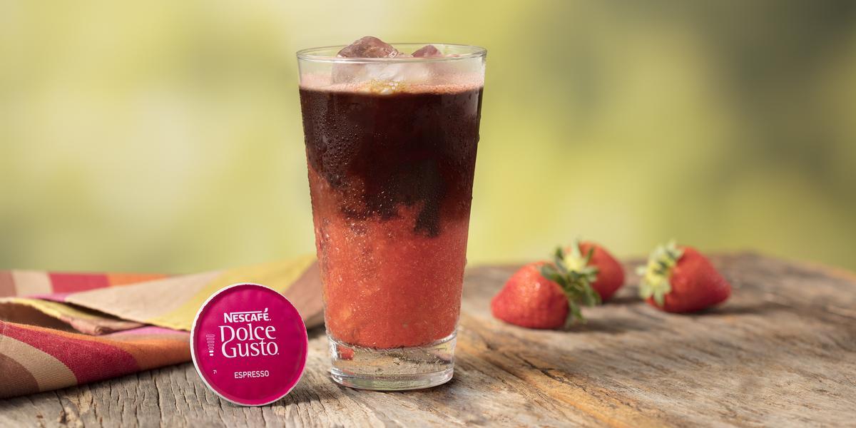 Fotografia em tons de rosa em uma bancada de madeira com um pano listrado colorido, um copo de vidro grande com o espresso gelado com morangos, uma cápsula de espresso e morangos espalhados na mesa.