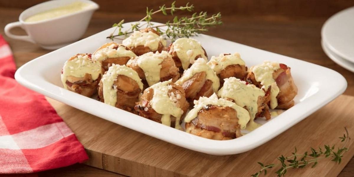 Fotografia em tons de vermelho em uma mesa de madeira com um pano xadrez vermelho, uma tábua de madeira ao centro com um recipiente retangular branco om os medalhões de frango com molho de mostarda e ervas. Ao fundo, um potinho com queijo ralado.