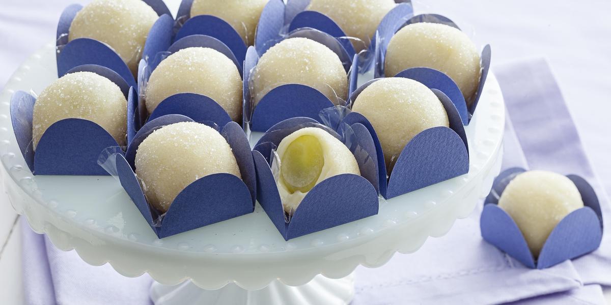 Fotografia em tons de branco e azul de uma bancada branca com paninho azul, sobre ele uma bailarina branca com docinhos de brigadeiro branco com uva verde dentro de forminhas quadradas azuis.