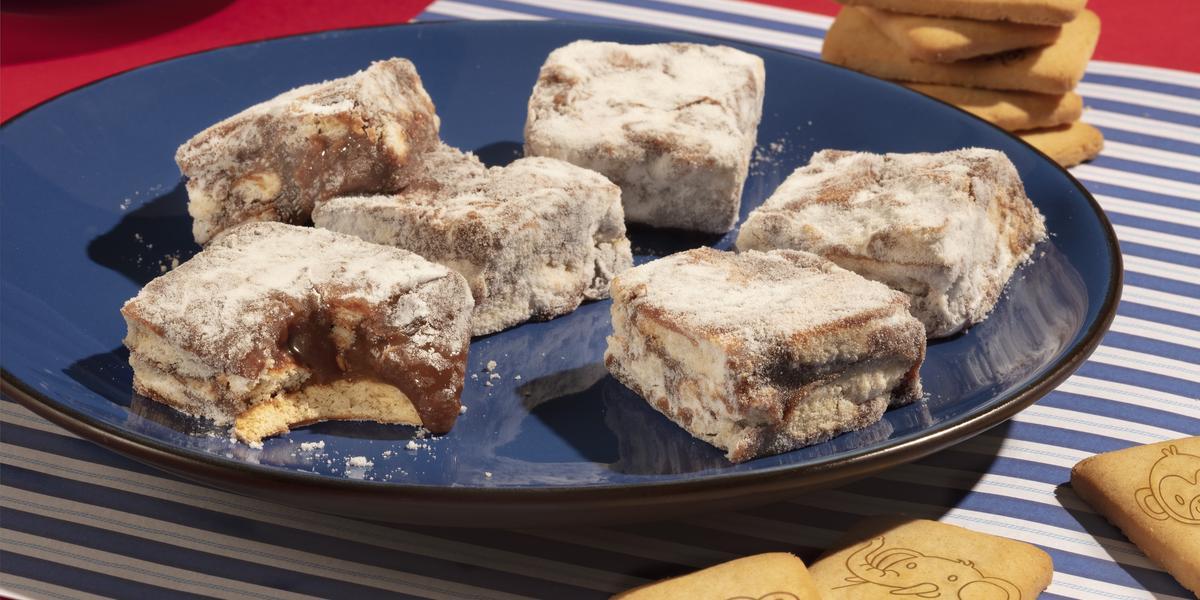 Fotografia em tons de azul e vermelho de uma bancada vermelha com paninho listrado de azul e branco, sobre ele um prato azul escuro com palha italiana de biscoito passatempo. Ao fundo biscoitos passatempo leite espalhados.