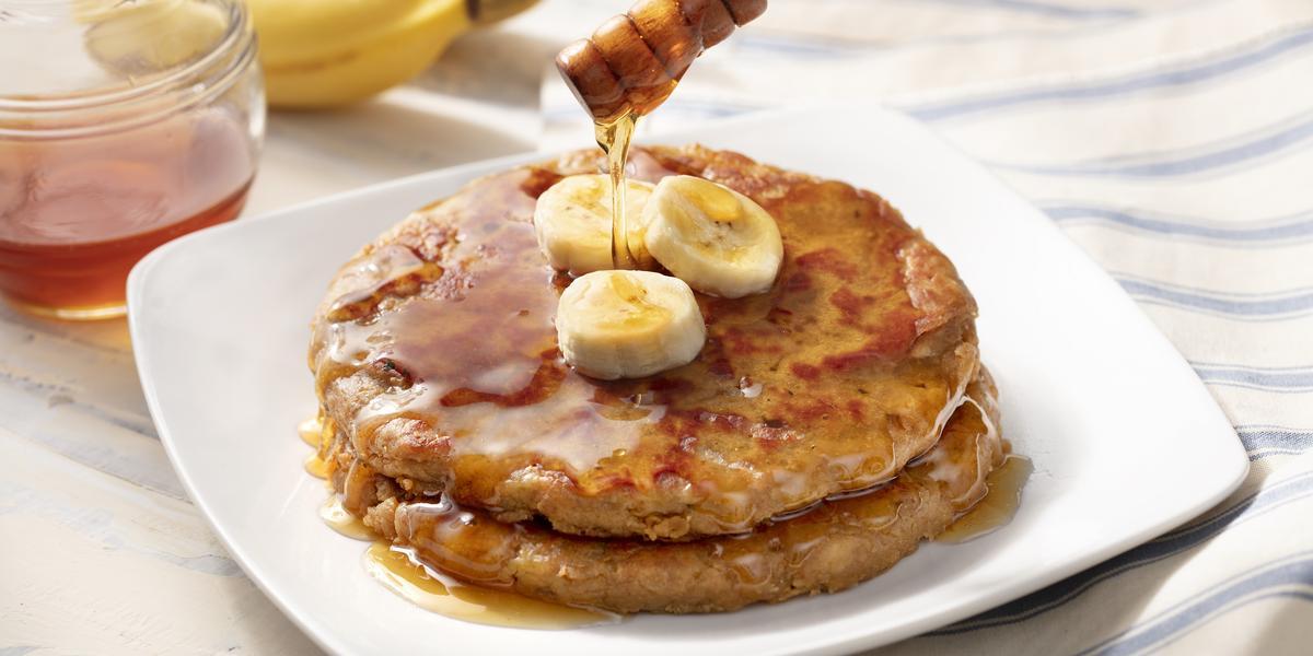 Fotografia me tons de branco de uma bancada de madeira, sobre ele um paninho listrado azul e branco com um prato quadrado com duas panquecas, mel e bananas. Ao fundo duas bananas e um recipiente de vidro com mel.