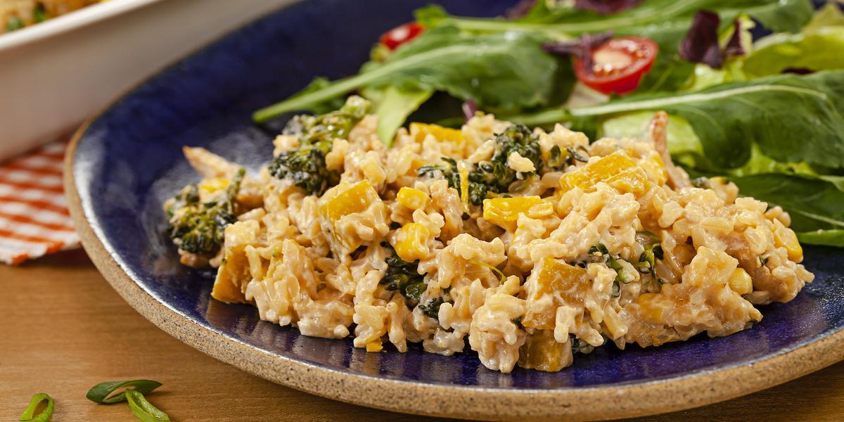 Fotografia em tons de marrom e azul de uma bancada de madeira, sobre ela um prato redondo azul com arroz e salada de folhas. Ao fundo um recipiente branco.
