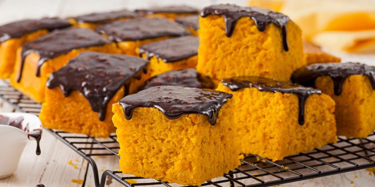 Fotografia em tons de amarelo e preto de uma bancada de madeira com um potinho branco com calda de chocolate, ao lado uma grade preta com fatias quadradas de bolo de cenoura com calda de chocolate em cima, ao fundo, um pano amarelo.