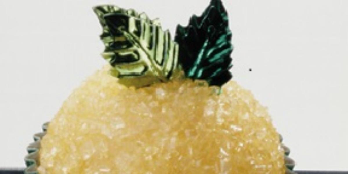 Fotografia em tons de amarelo e verve de um docinho em uma forminha verde, decorado com açúcar e duas folhinhas verdes.