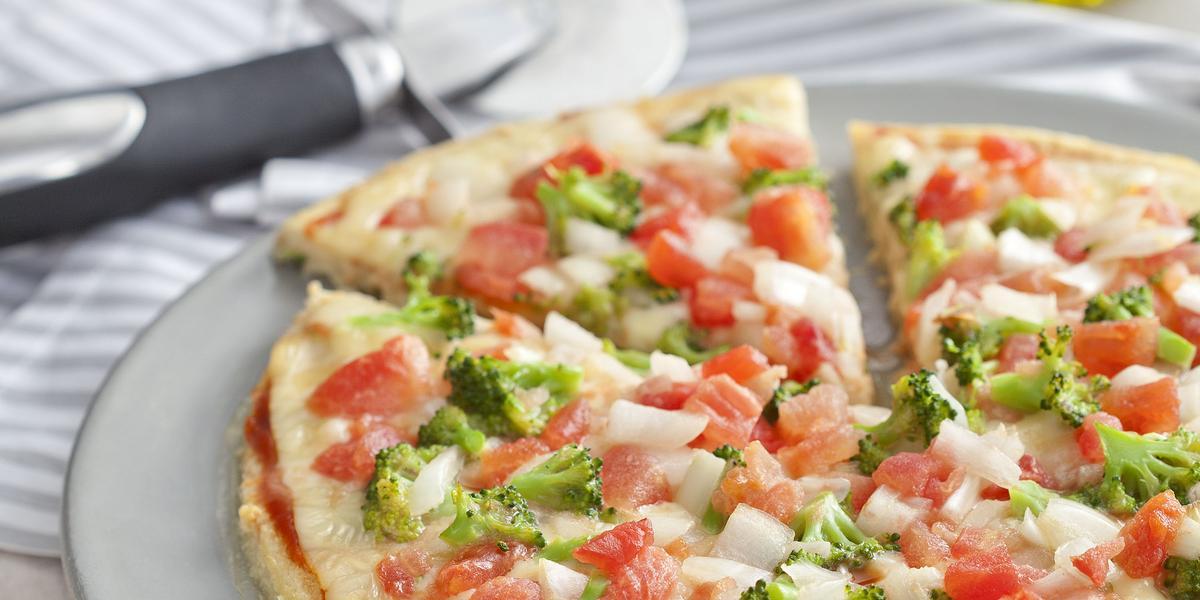 fotografia em tons de branco de uma bancada vista de frente, contém um prato redondo e branco com uma pizza com pedaços de tomates e brócolis ao fundo uma jarra com azeite.