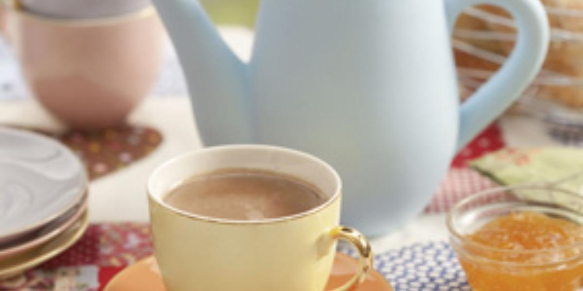 foto em tons de marrom, bege e azul tirada de um pratinho bege com uma xicara bege que contém o chocolate quente dentro. Ao fundo um bule azul