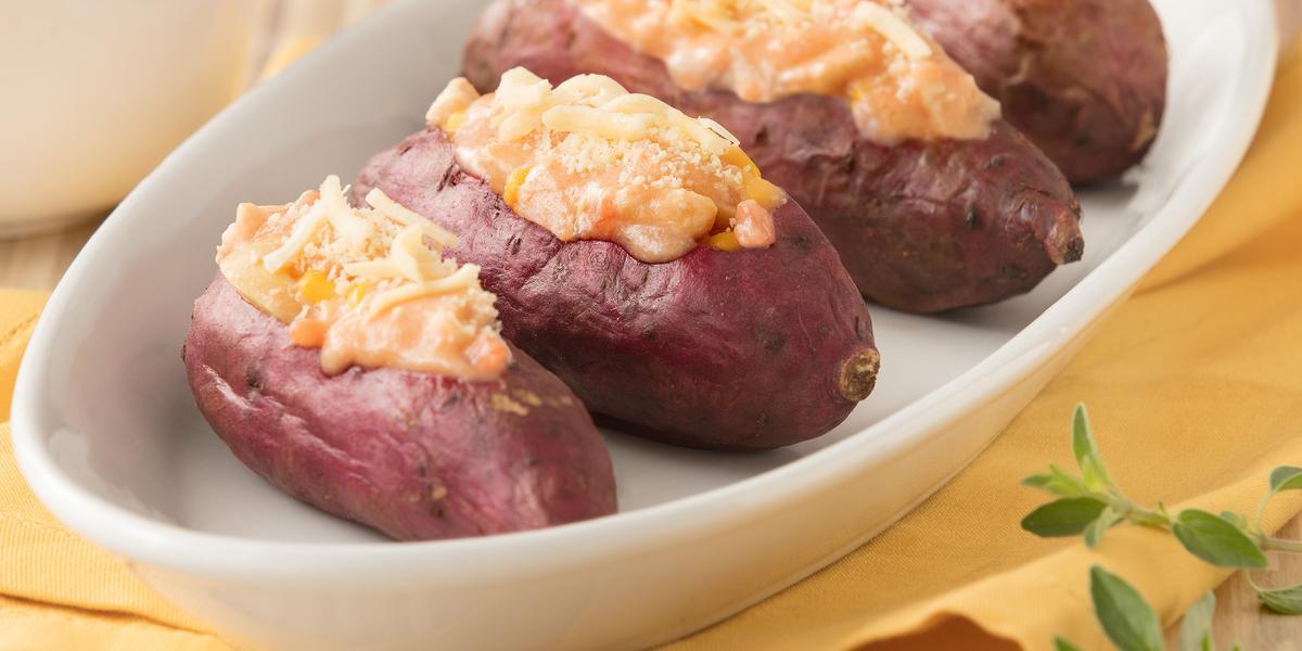 Foto de 4 batatas doces com recheio de frango cremoso dentro de um recipiente oval na cor branca, em cima de uma toalha amarela