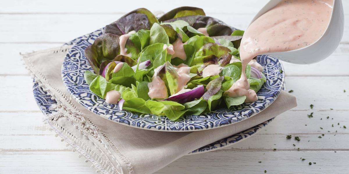 Fotografia em tons de azul, rosa e verde de uma bancada de madeira branca com paninho branco e um prato azul desenhado, sobre ele uma salada de alface com o molho rose e um recipiente despejando o molho sobre a salada.