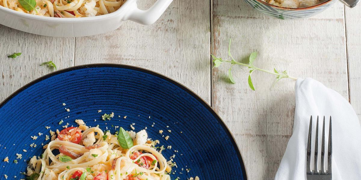 Fotografia em tons de azul em uma mesa de madeira clara com um guardanapo branco, um prato azul redondo com o macarrão com tomates e anchova.