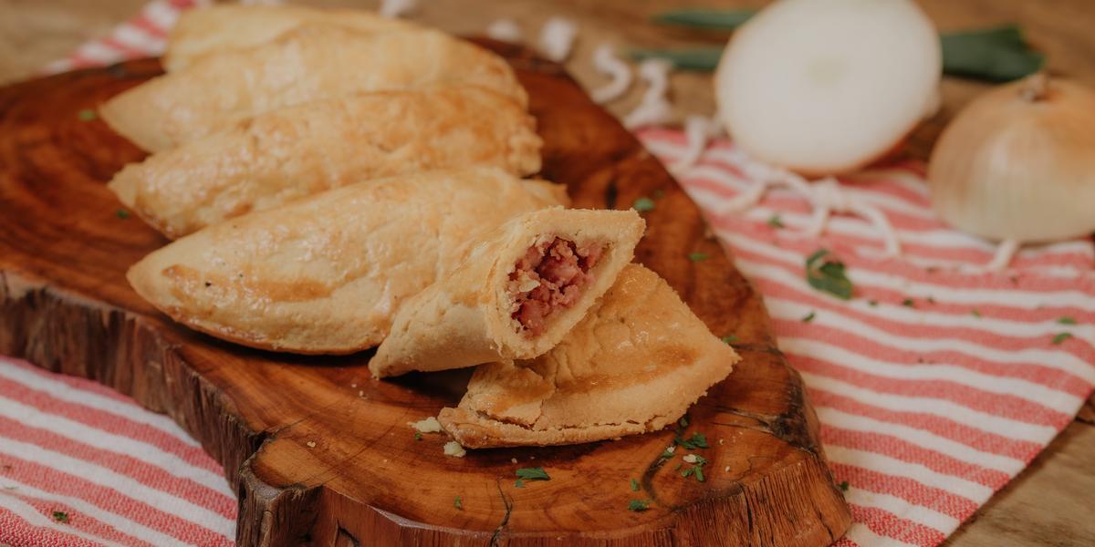 Fotografia em tons de marrom e vermelho de uma bancada de madeira com um paninho listrado vermelho e branco, sobre ele uma tabua de madeira com mini empadas. Ao fundo uma cebola cortada ao meio.