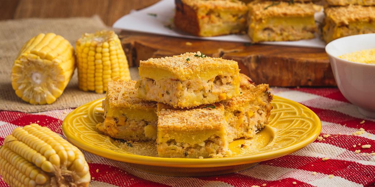 Foto de uma bancada de madeira com uma toalha vermelha quadriculada, com um prato amarelo no centro e pedaços da torta de milho com frango. Há milhos decorando a cena e, ao fundo, mais pedaços de torta sobre uma tábua de madeira.