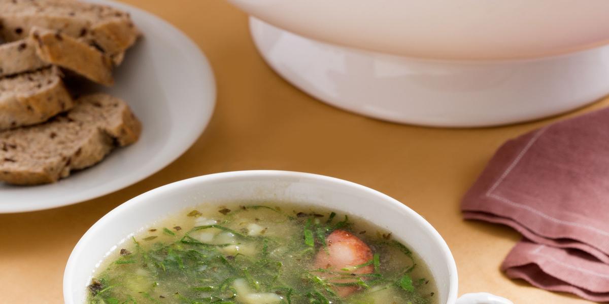 Foto de um recipiente redondo, como uma xícara, só que maior, com caldo verde dentro, em cima de um prato branco