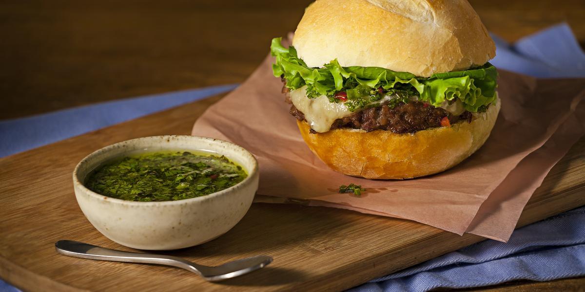 Fotografia em tons de azul em uma bancada de madeira, com uma tábua de madeira, um guardanapo marrom, um hambúrguer caseiro em cima dele. Ao lado, um potinho com molho chimichurri.