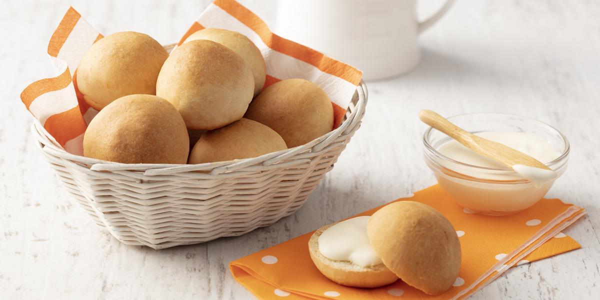 Fotografia em tons de laranja e branco de uma bancada branca com um paninho laranja, sobre ele um pãozinho aberto recheado e um recipiente de vidro com requeijão. Ao lado uma cesta com um paninho laranja e branco com os pães.